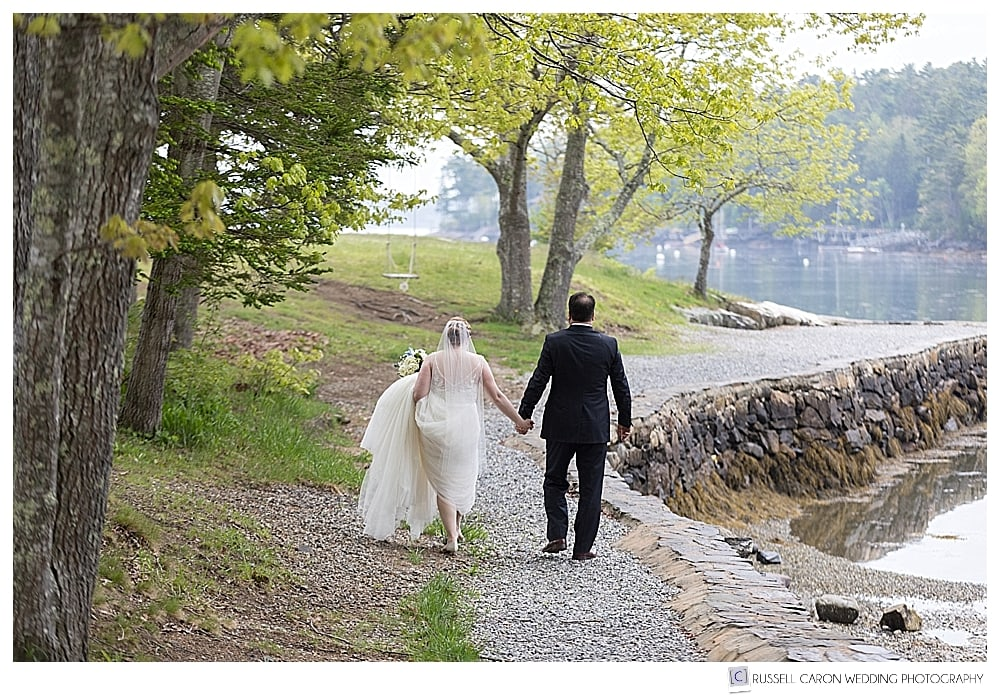 bride and groom walking together towards a cove in boothbay harbor maine