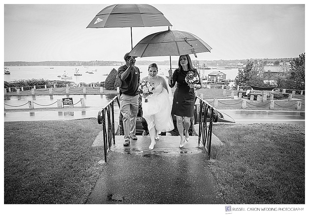 black and white photo of bride arriving at church in the rain