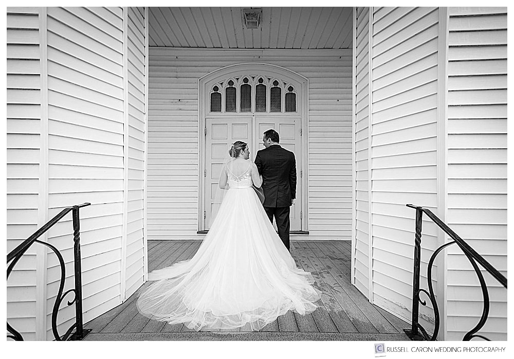 black and white photo of bride and groom standing at the door of Our Lady Queen of Peace Church Boothbay Harbor Maine