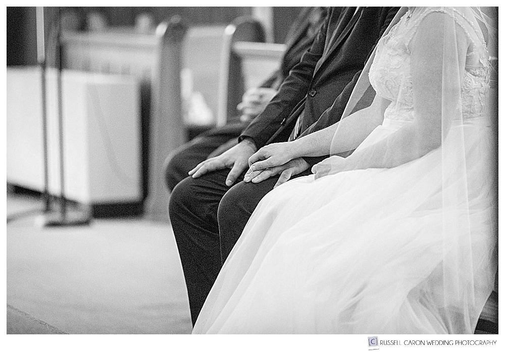 bride and groom hold hands during our lady queen of peace church wedding ceremony
