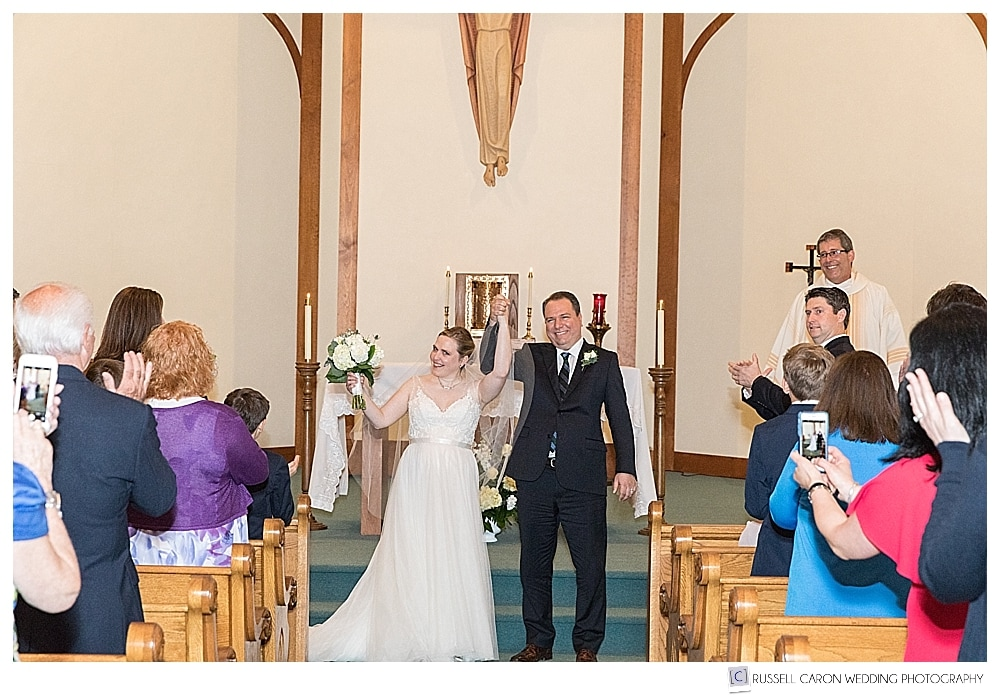 bride and groom during recessional at our lady queen of peace church boothbay harbor maine