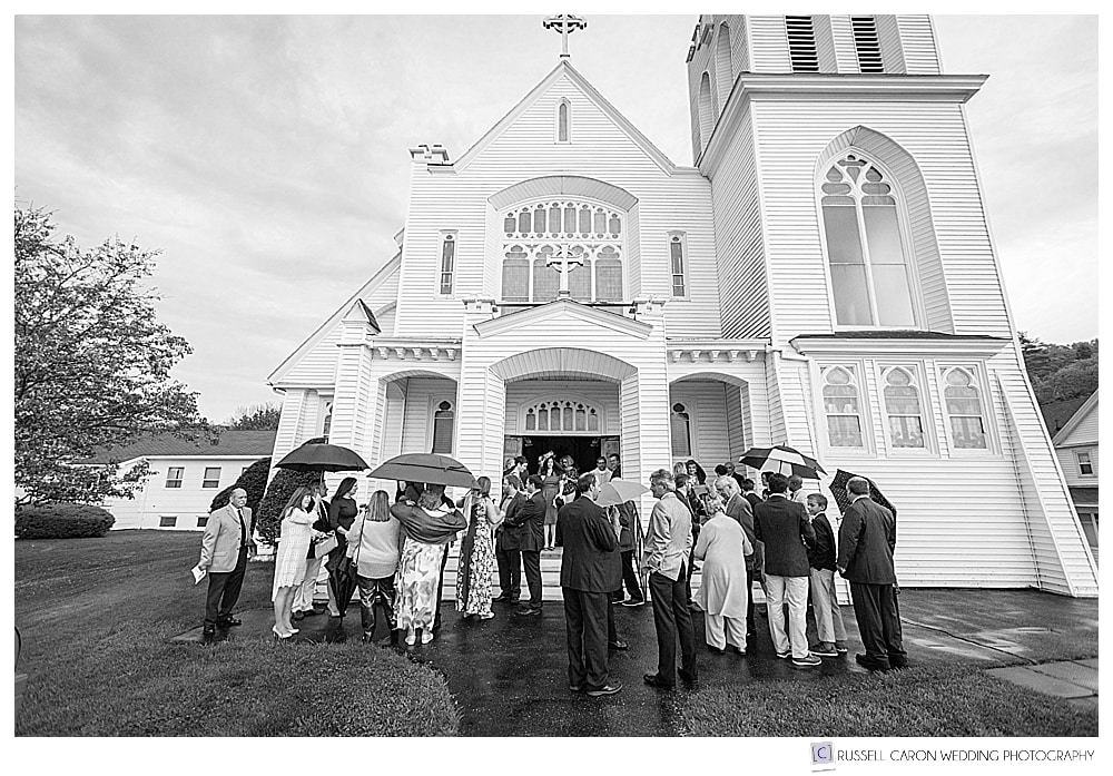 guests outside Our Lady Queen of Peace Church with umbrellas during late spring boothbay harbor wedding