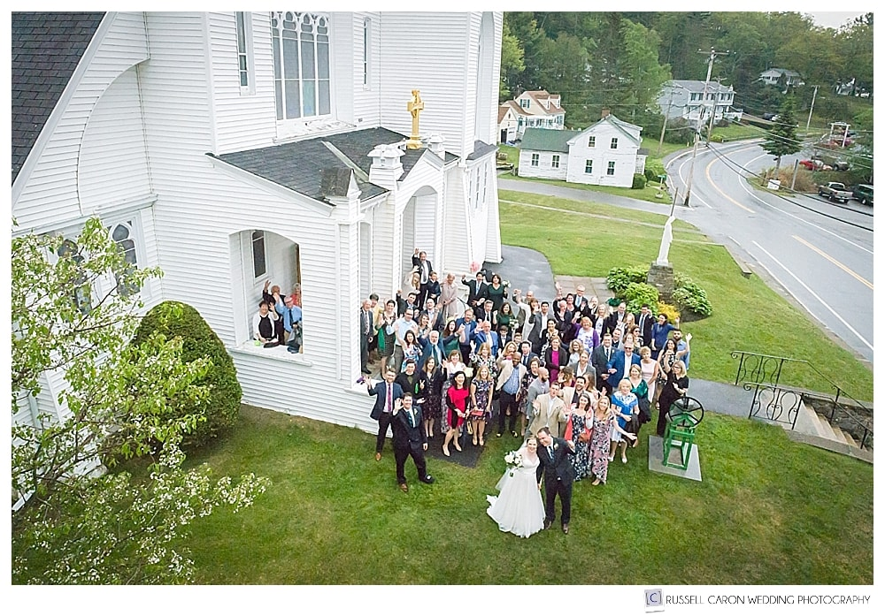 maine drone wedding photographer takes drone photo of guests outside our lady queen of peace church