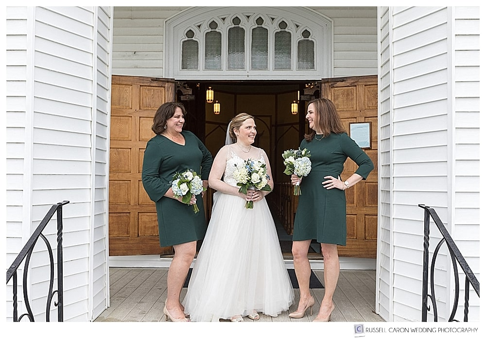 bride and bridesmaids stand on church steps