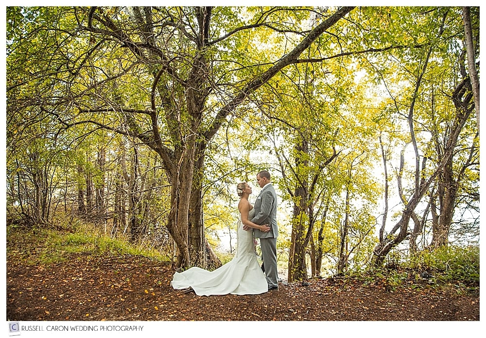 Bride and groom standing together in the woods of Acadia National Park, Maine