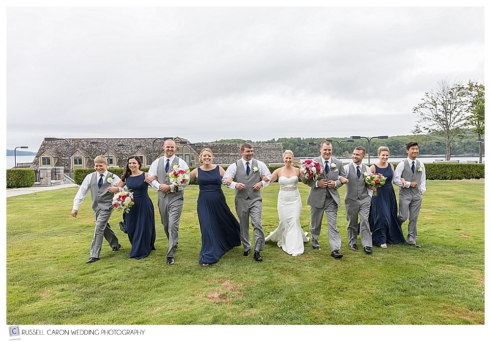 bridal party walking arm in arm