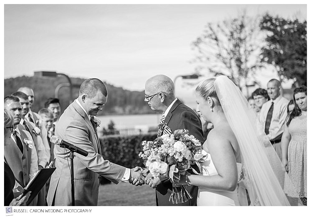 Father of the bride, and groom , shake hands at the altar