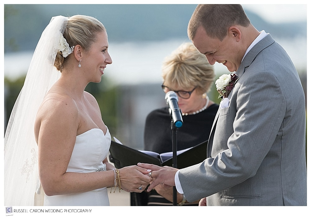 groom laughing as bride tries to put wedding band on his finger