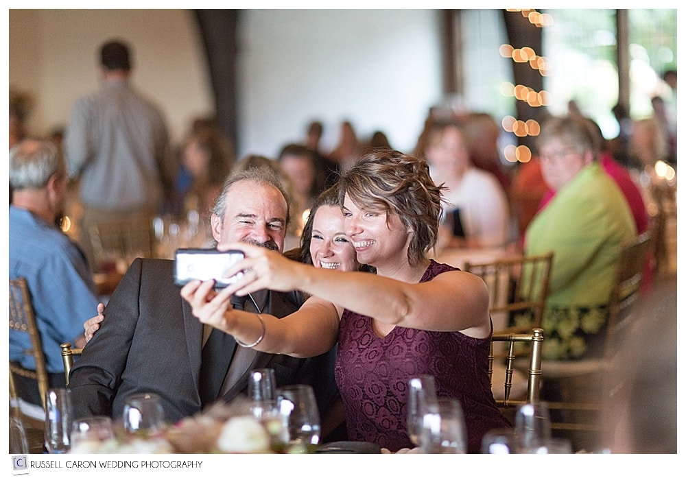 Wedding guests taking a selfie during wedding reception