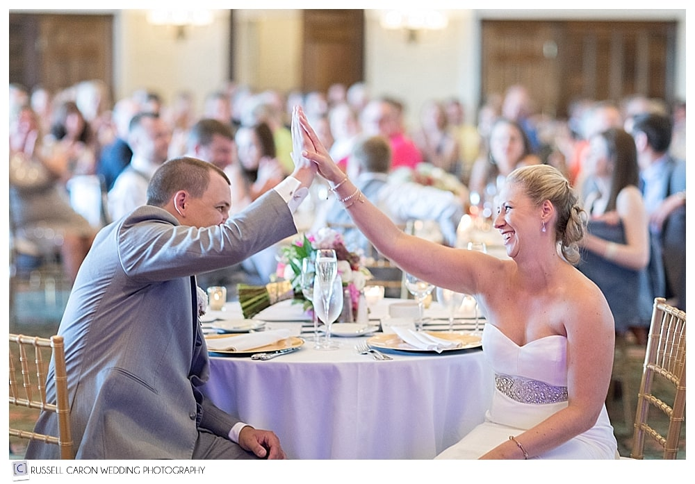 Bride and groom high five each other