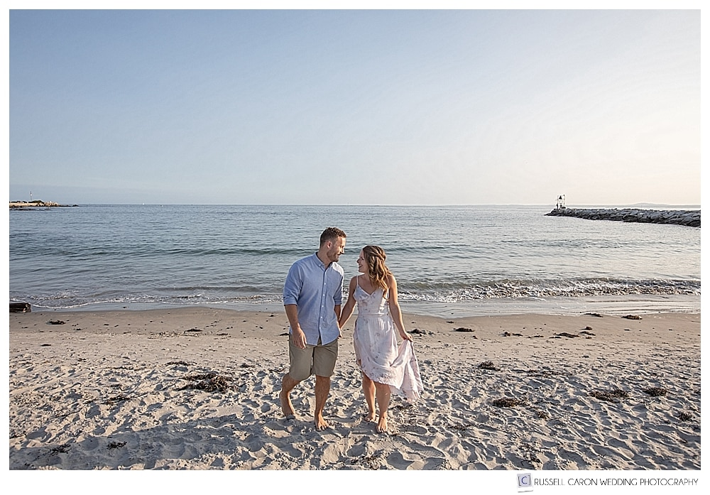 man and woman walking on Colony Beach in Kennebunkport Maine during beachy Kennebunkport engagement photos