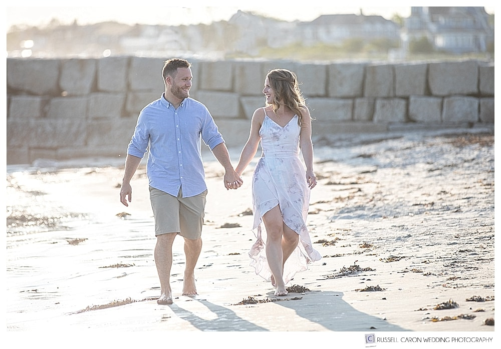 man and woman walking on Colony Beach, Kennebunkport, Maine, during their beachy Kennebunkport Maine engagement session