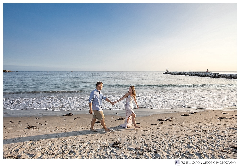 man and woman walking near near the water at Colony Beach during their Kennebunkport Maine engagement session