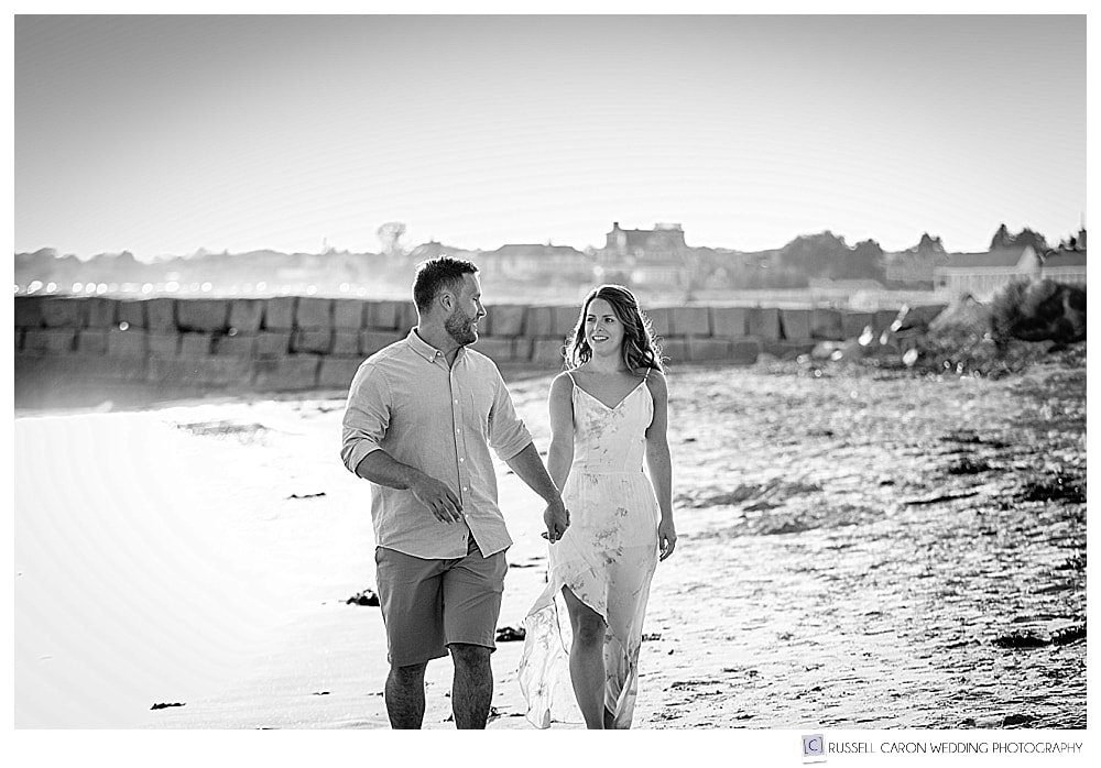 black and white photo of man and woman walking on Colony Beach during a summery, beachy Kennebunkport engagement session, Kennebunkport Breakwater