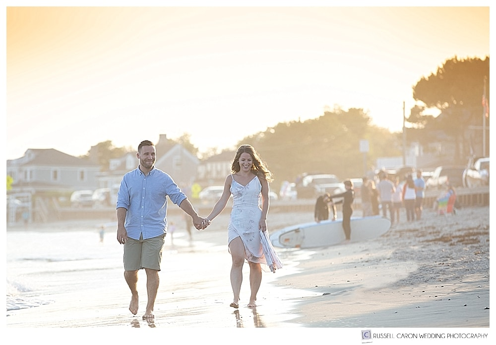 man and woman walking and holding hands in the golden light at Mother's Beach, Kennebunk, Maine
