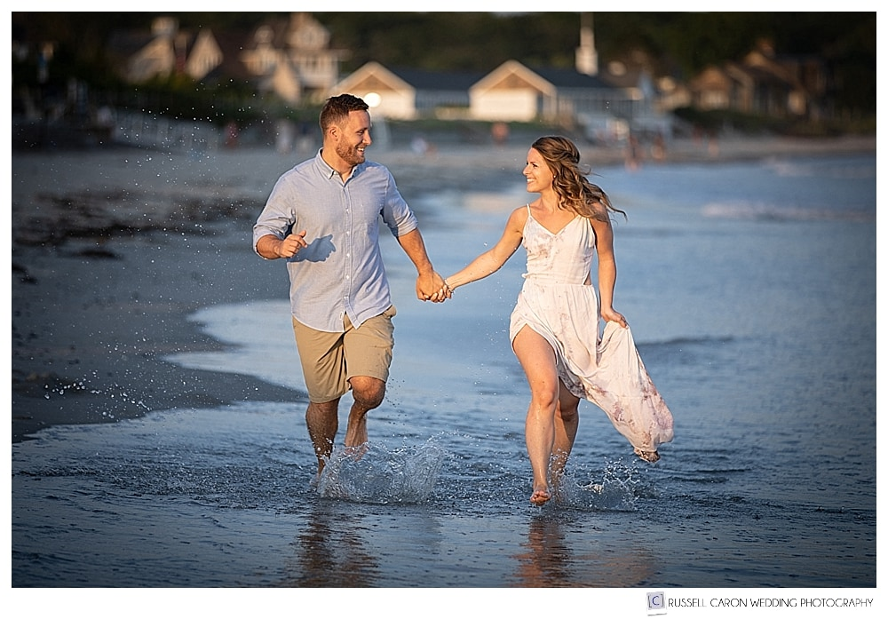 man and woman running in the water at the beach during their beachy Kennebunkport Maine engagement photo session