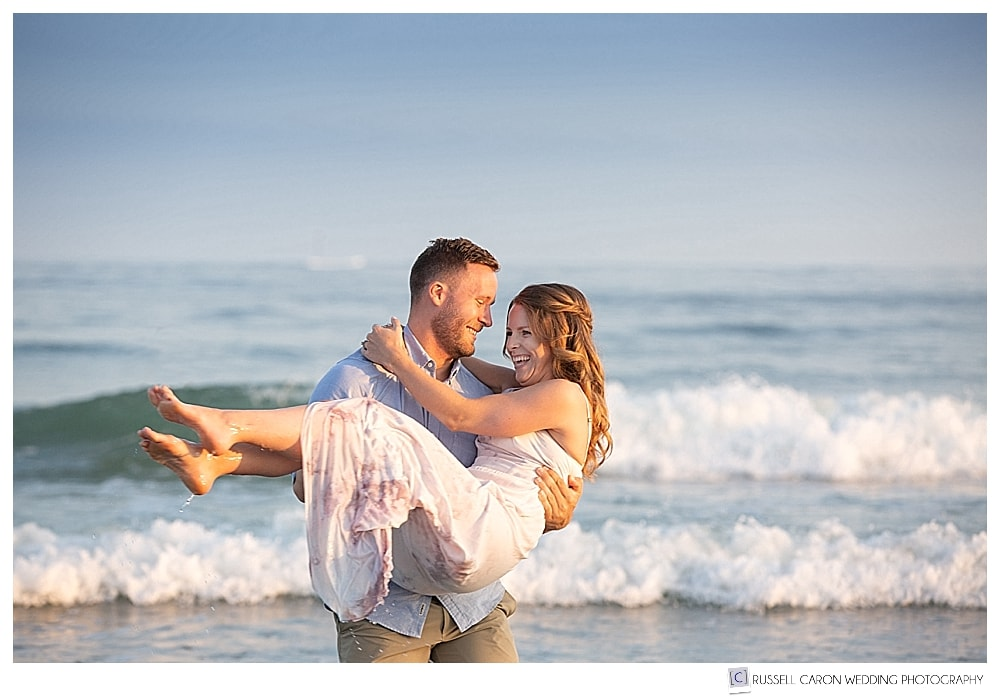 man holding woman at the beach with waves in the background