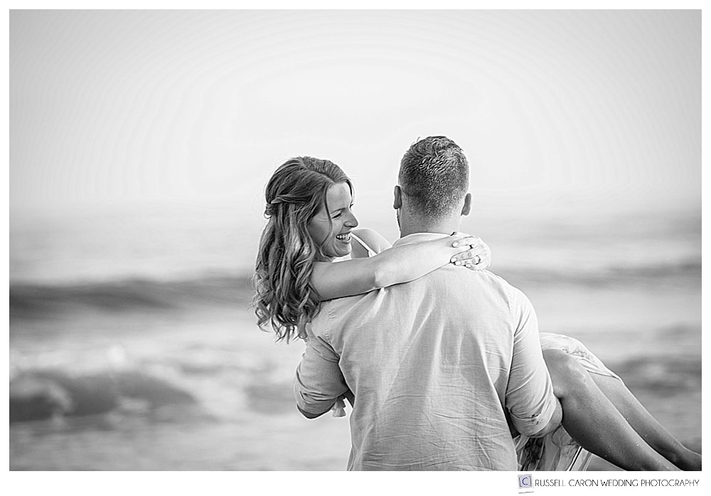 black and white photo of man holding woman in his arms at the beach