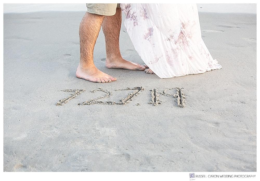 man and woman standing in front of wedding date written in sand