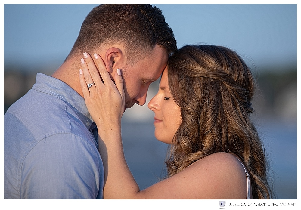 man and woman standing forehead to forehead in the golden light of sunset at their Kennebunkport Maine engagement session