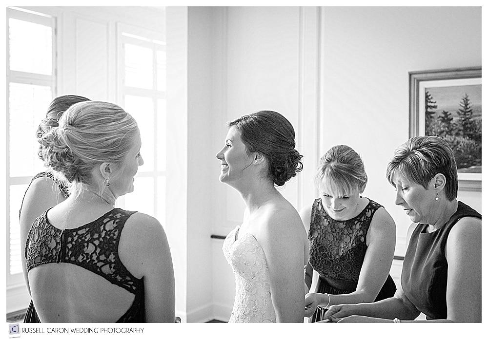 bridesmaids helping bride get dressed
