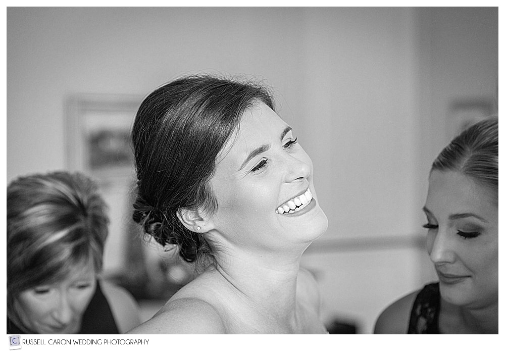 bride laughing as she gets into her wedding dress