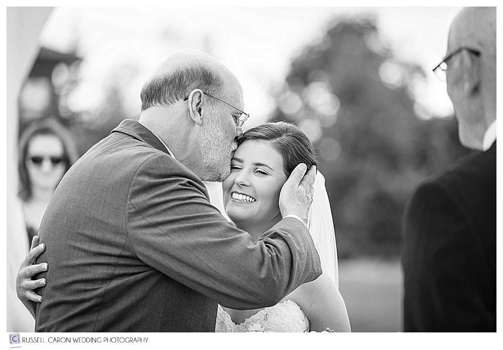 father of the bride, kisses the bride