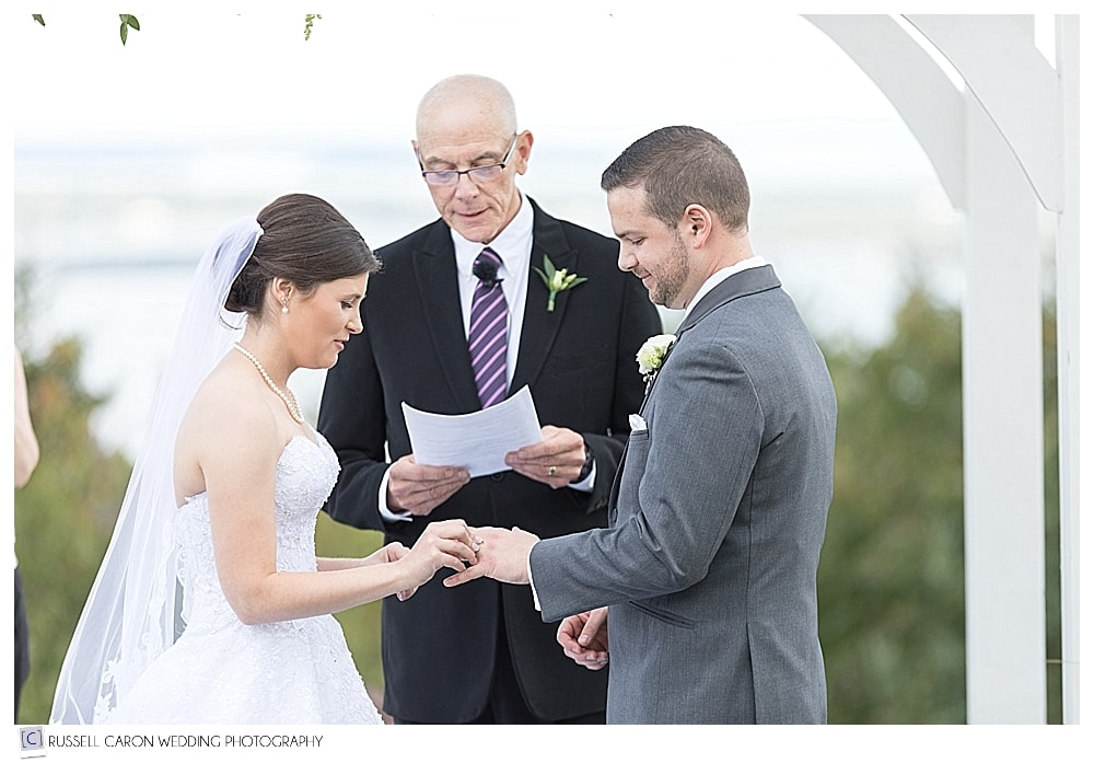 bride puts ring on grooms finger during beautiful Point Lookout wedding ceremony, Northport, Maine
