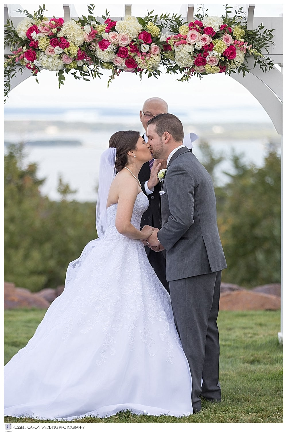 bride and groom's first kiss during their beautiful Point Lookout wedding, outdoors on the lawn, at Northport, Maine