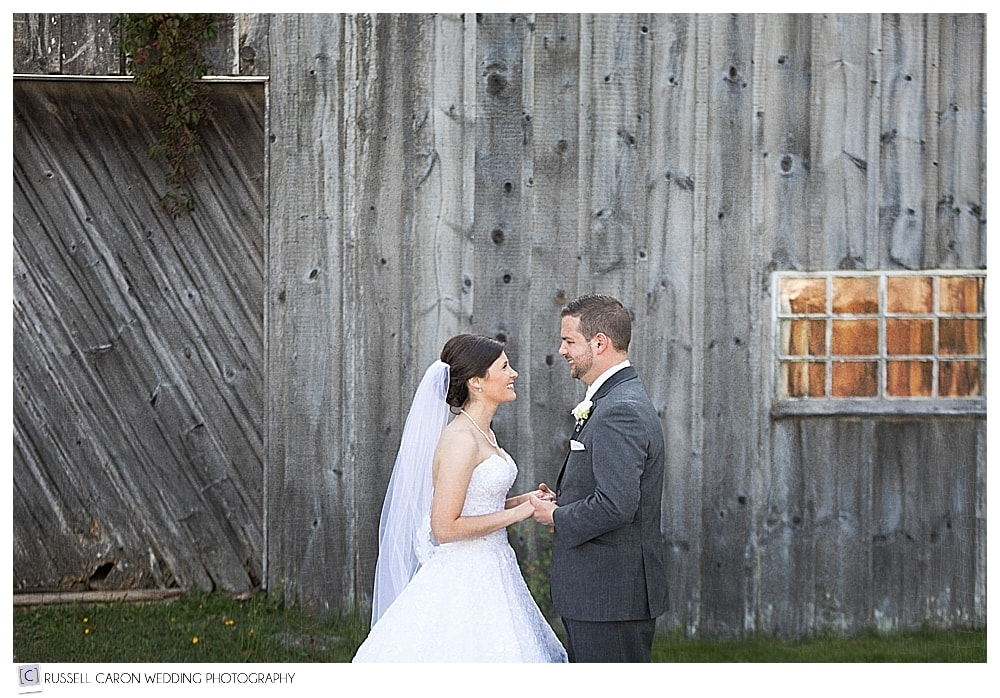 bride and groom in front of old Maine barn