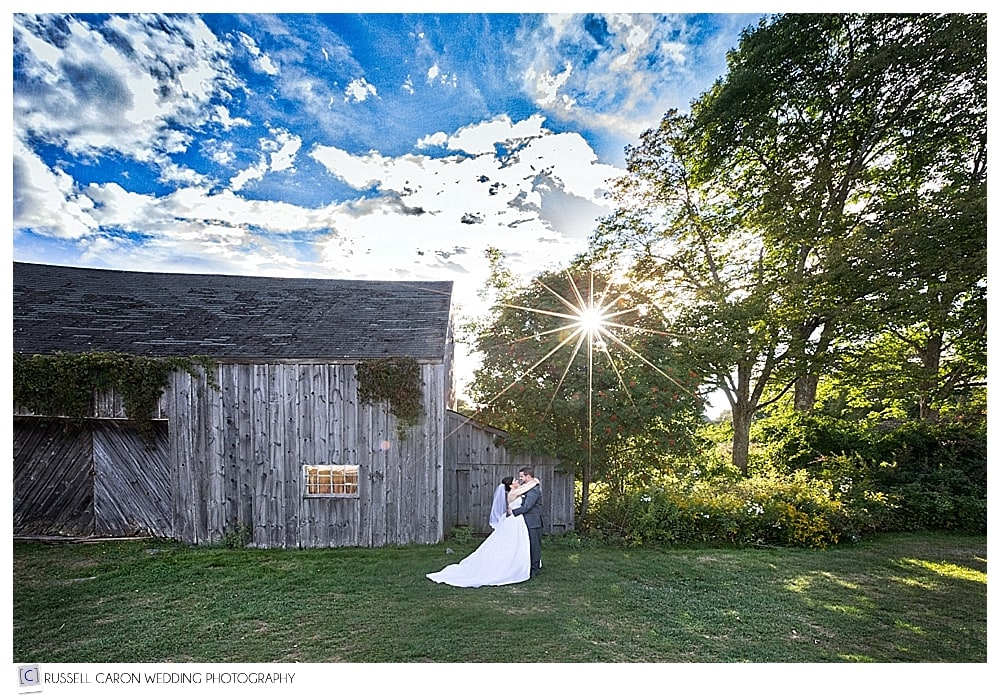 bride and groom in front of weathered Maine barn