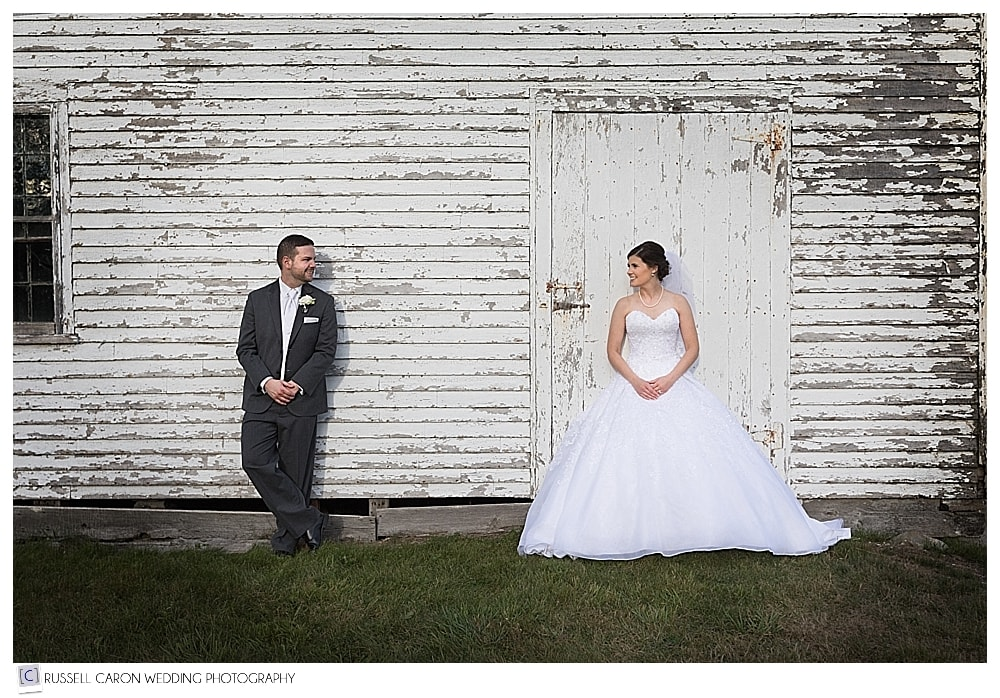 Bride and groom standing in front of an old house