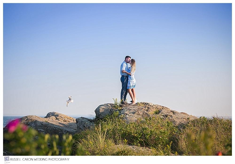 couple kissing on the rocks near the ocean