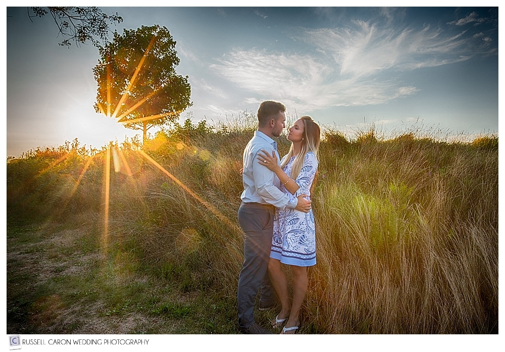 man and woman in a field at sunset