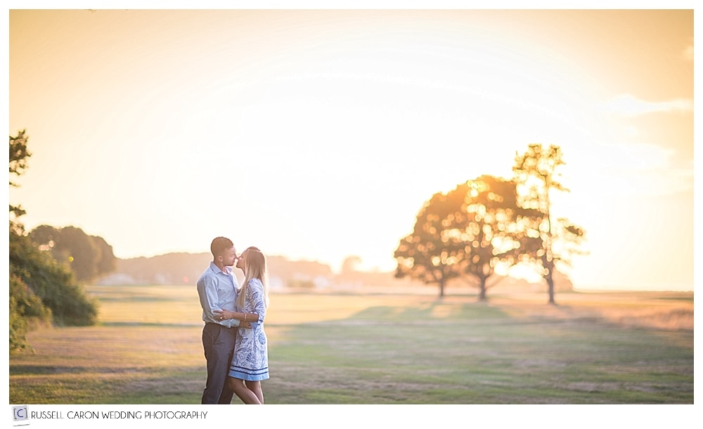 man and woman standing together during sunset