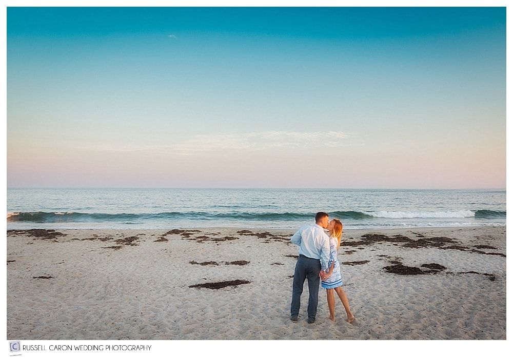 couple walking and kissing on the beach