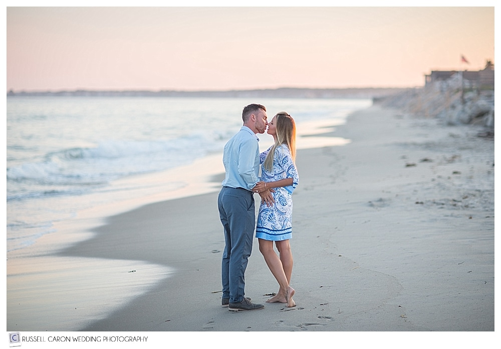 engaged couple kissing at the water's edge