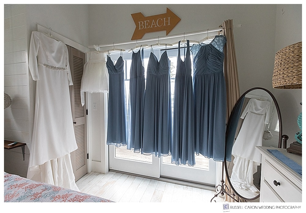 bridal gown and bridesmaids dresses hanging in a bridal suite