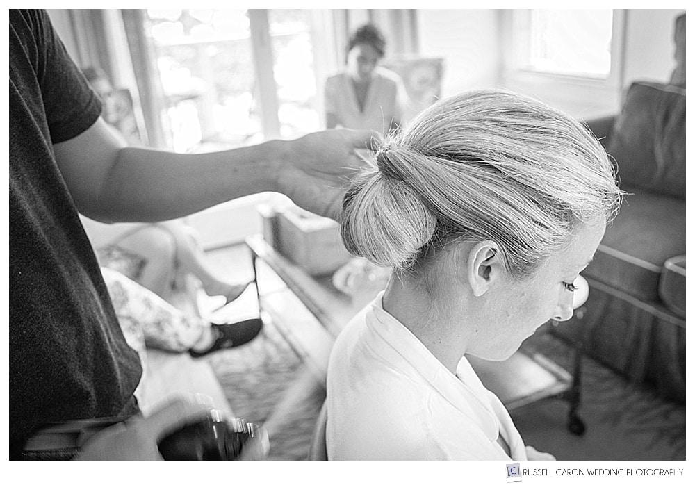black and white photo of bridal prep with bride getting hair done