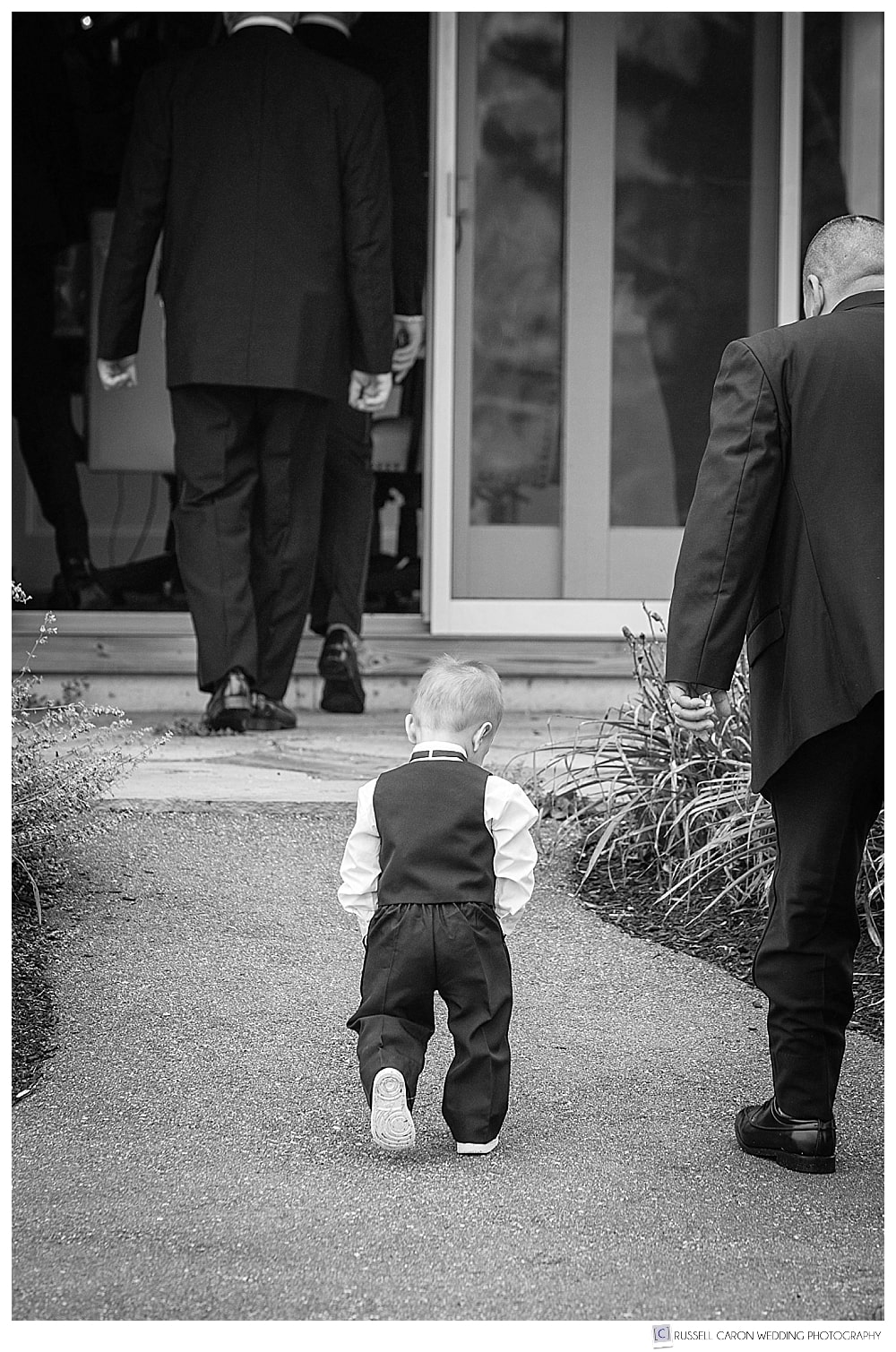 little boy walking with men