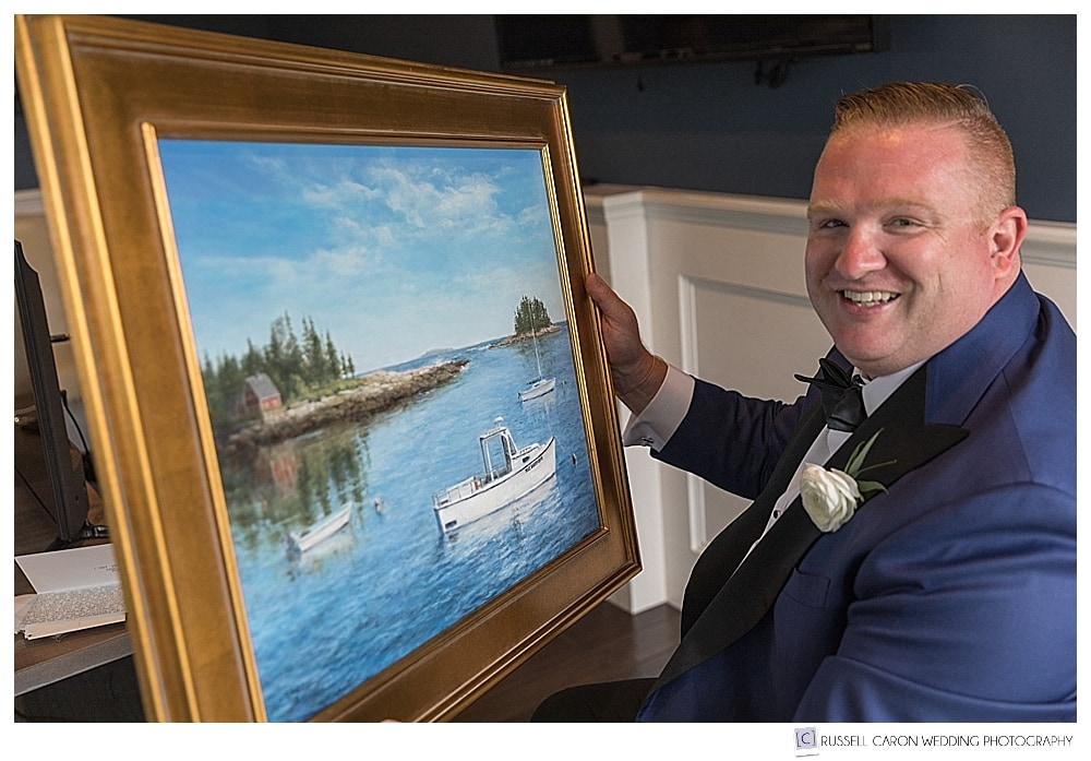 groom holding a painting of a seascape