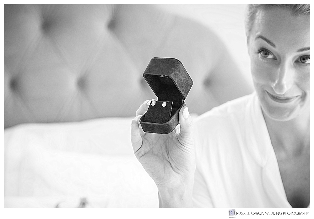 black and white photo of bride holding up a jewelry box with earrings