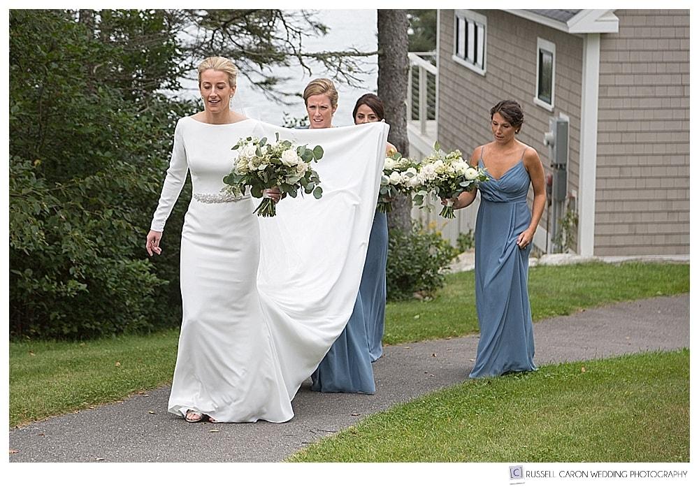 bride and bridesmaids walking, with bridesmaid holding dress