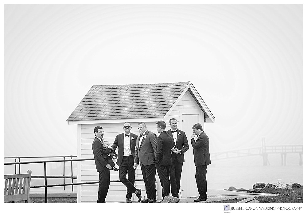 groomsmen waiting for the ceremony, standing near a dock house