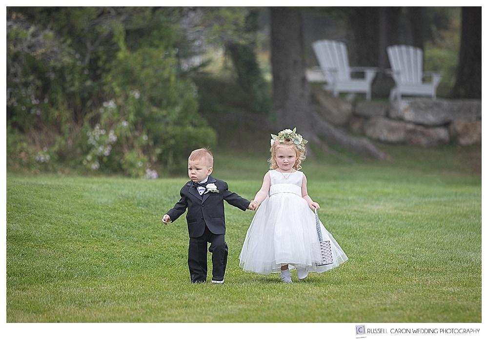 flower girl and ring bearer walking down a grass aisle
