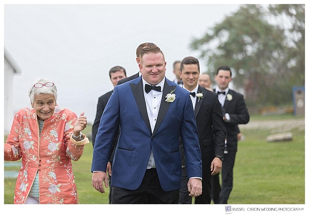 groom and groomsmen walking into outdoor ceremony