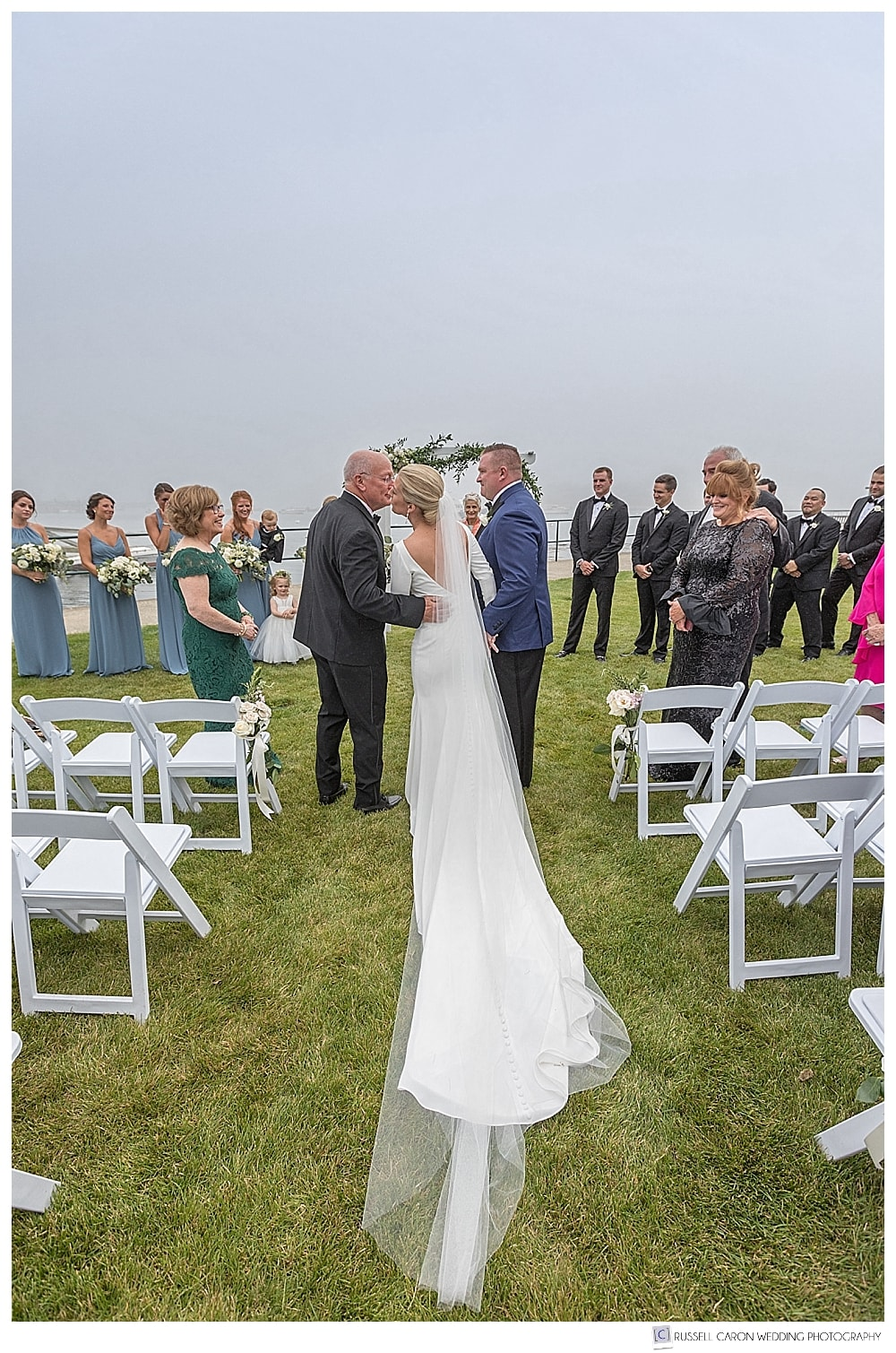 bride and her father reach the groom during an outdoor ceremony at the Newagen Seaside Inn, Southport Island, Maine