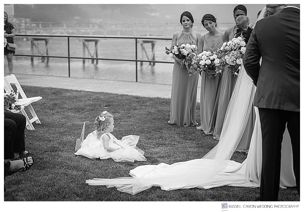 black and white photo of flower girl playing on a lawn while wedding ceremony in progress