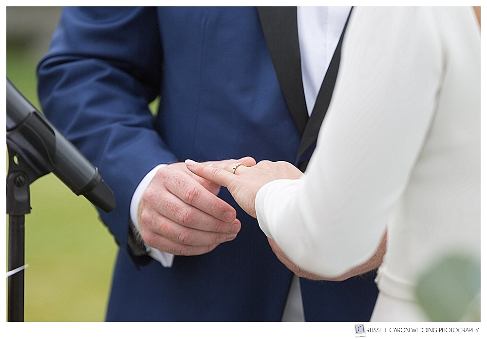 groom places ring on brides hand during wedding ceremony