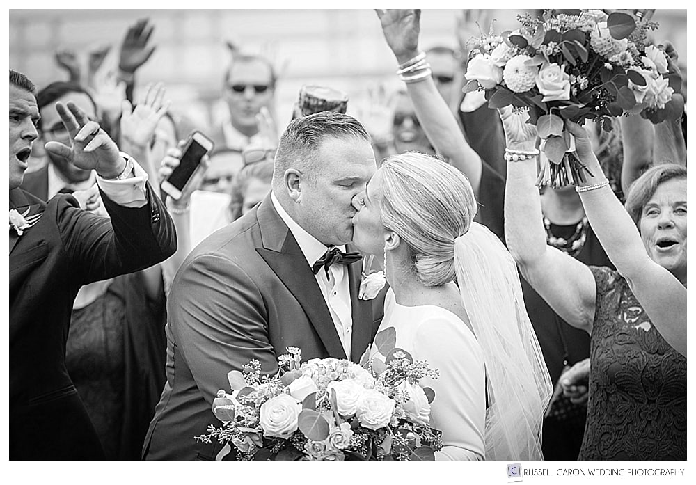 black and white photo of bride and groom kissing, surrounded by wedding guests